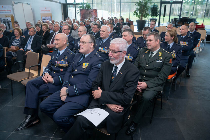Zaal met mensen in uniform en in civiel tenue.