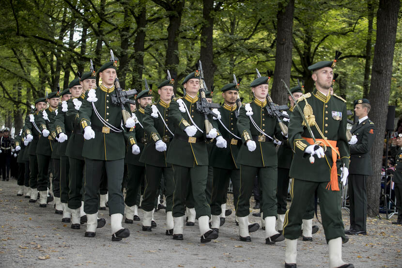Landmachtmilitairen marcheren in ceremonieel tenue.