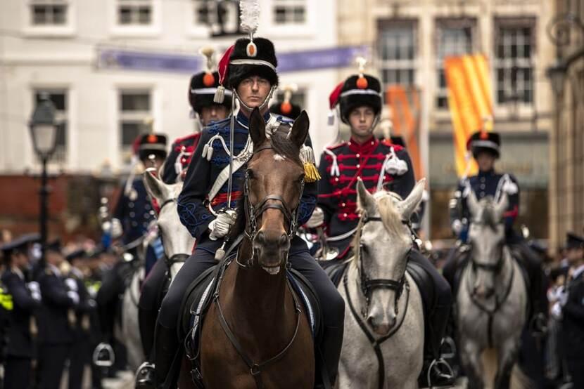 Militairen in ceremonieel tenue te paard.