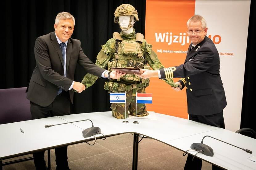 Kapitein ter zee Mark Spierings en Haim Delmar van Elbit Systems tekenen het contract. Tussen hen in een paspop in camouflagetenue.