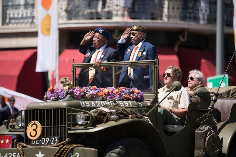 2 veteranen staan in jeep en salueren.