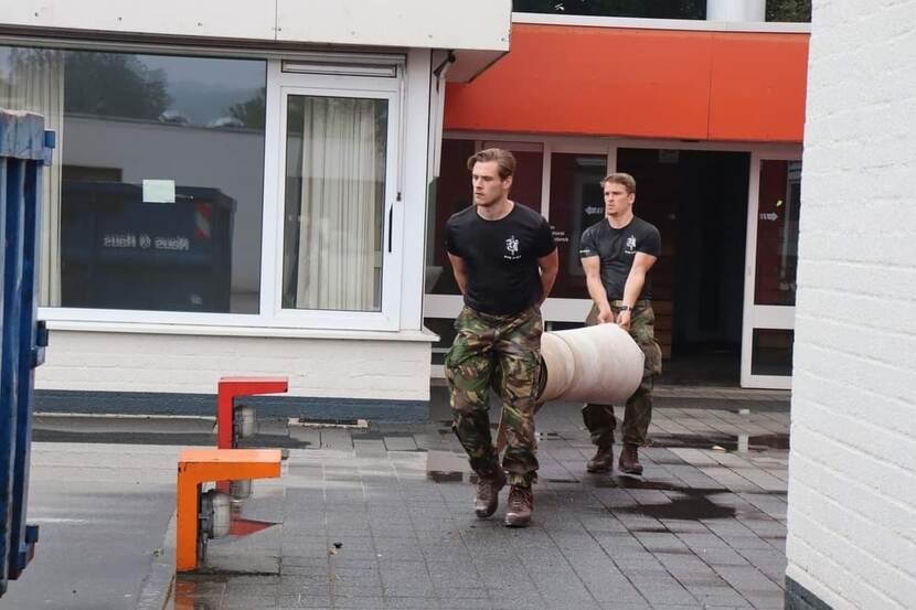 2 mannen sjouwen een rol vloerbedekking.