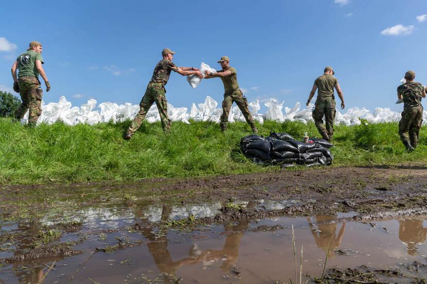 Militairen staan op een dijk en geven zandzakken aan elkaar door.