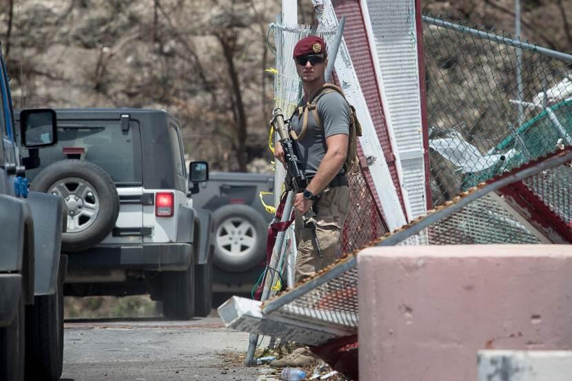 Militair met wapen staat aan de rand van een weg tussen omgevallen hekken, auto's passeren.