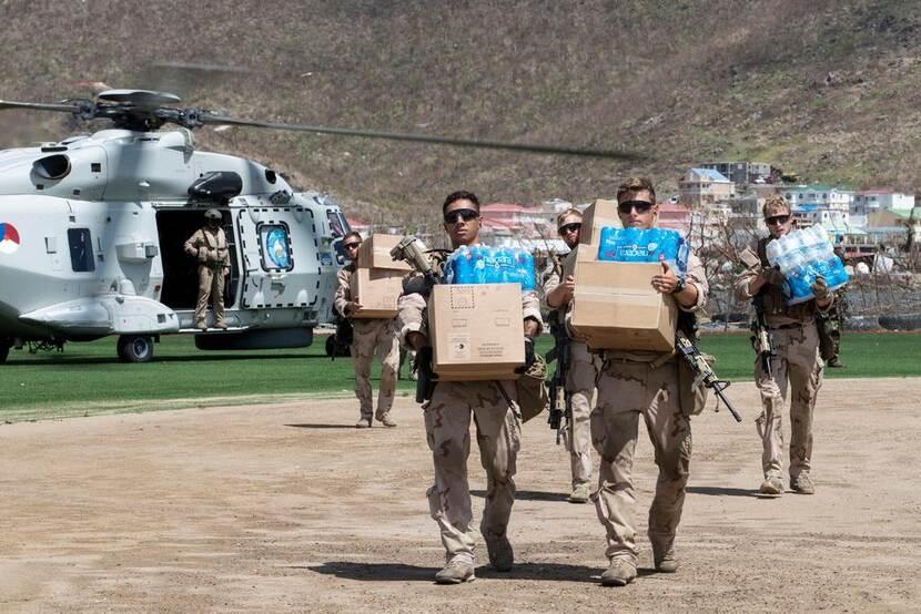 Nederlandse militairen dragen dozen met waterflessen, een helikopter op de achtergrond.