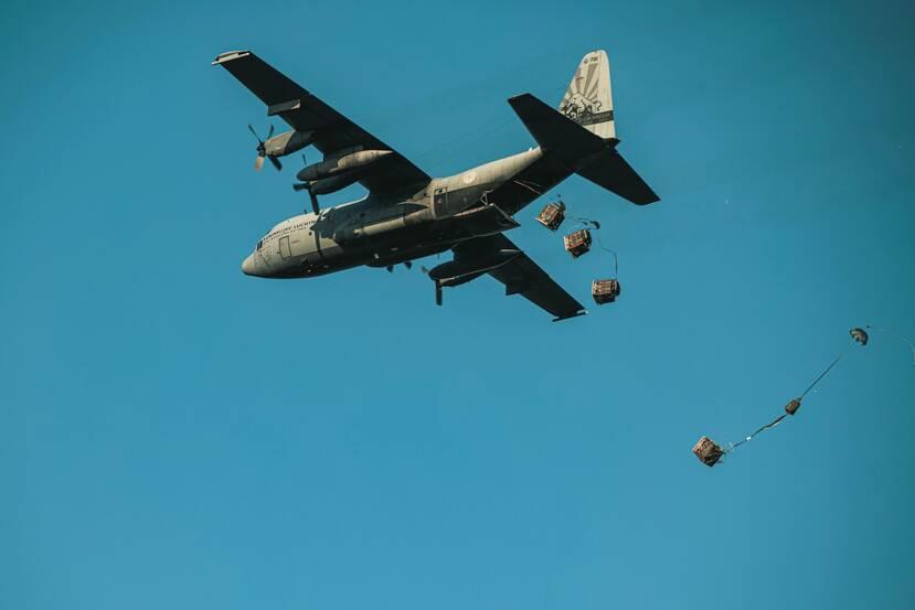 Vanuit een C-130 transportvliegtuig worden container delivery systems gedropt.