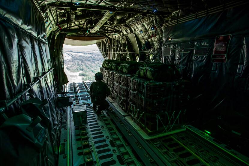 Container delivery systems staan in het geopende laadruim van een vliegende C-130 transportvliegtuig klaar voor dropping.