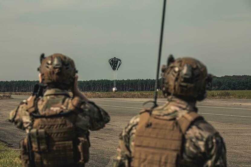 Luchtmobiele infanteristen zien toe op de landing van een gedropt container delivery system.
