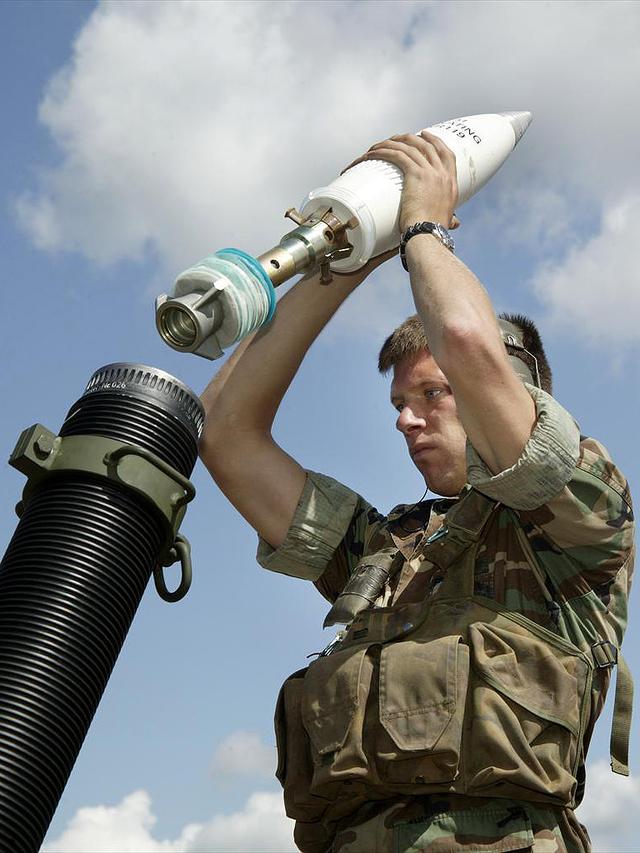 Een militair staat op het punt om een 120mm rookgranaat af te vuren.