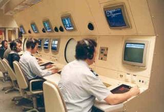 Personeel achter de beeldschermen in de Pharos II operation room in april 1994. Foto: NIMH